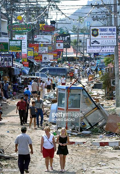 Foreign tourists walks past debris on the Tewewong road in the devastated Patong coastal district in Phuket 28 December 2004 after deadly tidal waves...