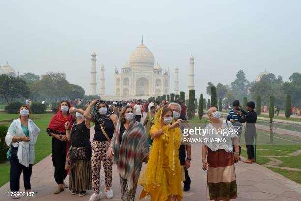 Foreign tourists wearing face masks visit the Taj Mahal under heavy smog conditions, in Agra on November 4, 2019. - As smog levels exceeded those of...