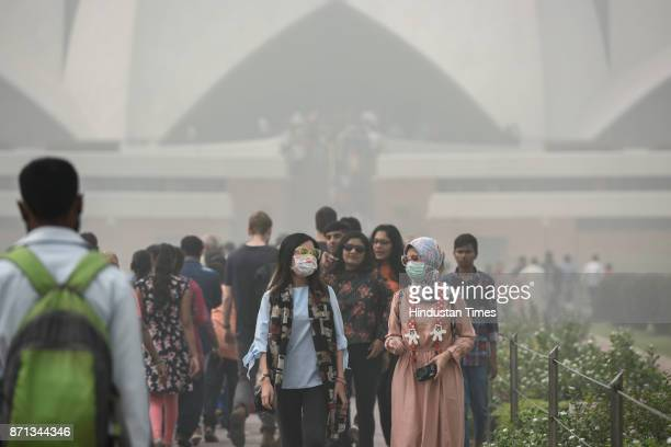 Foreign tourists wearing masks as they visit Lotus Temple on a smoggy morning on November 7 2017 in New Delhi India Delhi woke up to a thick brown...