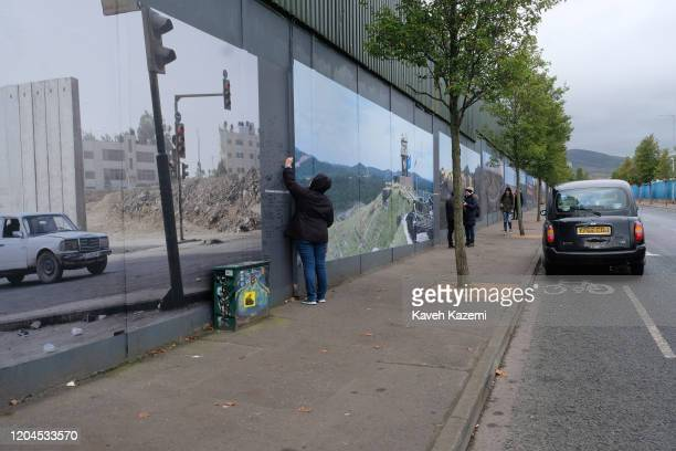 Foreign tourists write messages on the peace wall on the Cupar Way which runs between the Protestant and Catholic communities on October 30 2019 in...