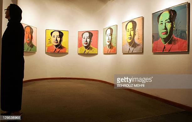 A foreign visitor looks at Andy Warhol's Portraits of Mao displayed at the Modern Art Movement exhibition at Tehran's Museum of Contemporary Art 01...