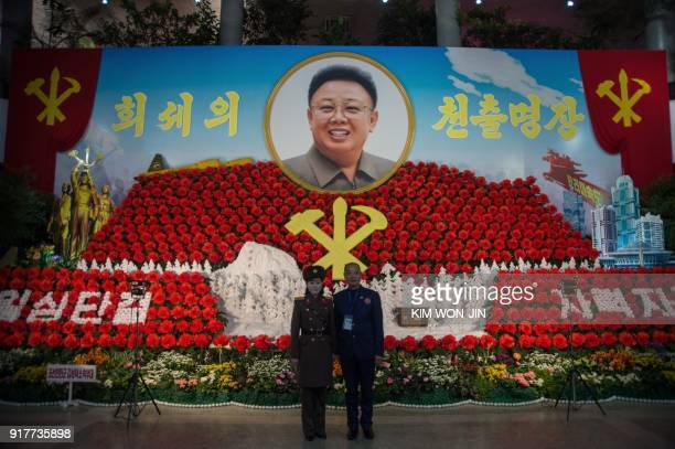 TOPSHOT A foreign visitor stands for a photo with a Korean People's Army soldier in front of a portrait of late North Korean leader Kim Jong IL at...