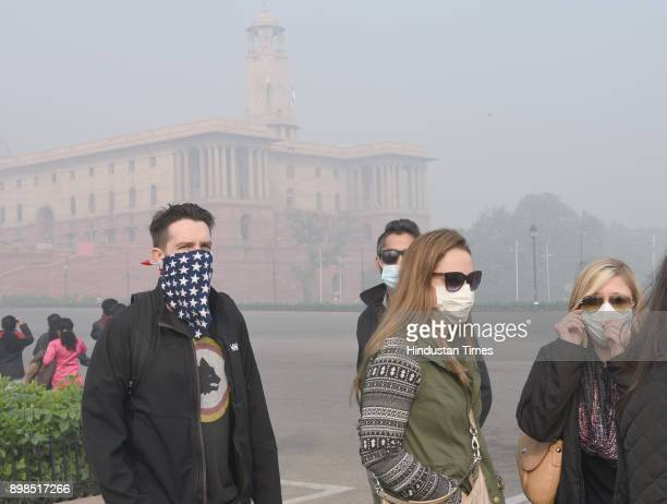 Foreign visitors taking precautions during smog and fog in the morning time 10 am at Vijay chowk on December 25 2017 in New Delhi India