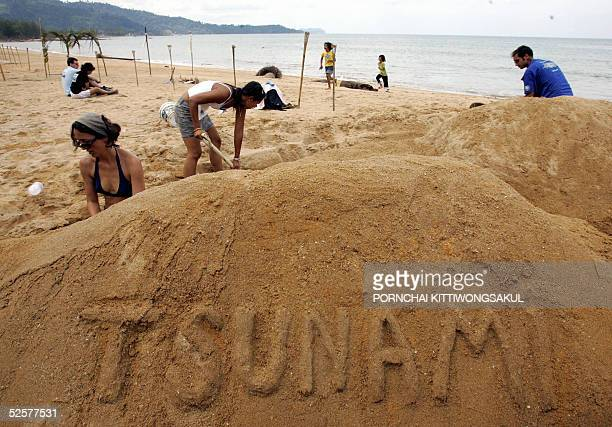 Foreign volunteers make symbolic of tsunami from sand during the 100 days tsunami memorial at Khao Lak in Phang Nga province southern of Thailand 02...