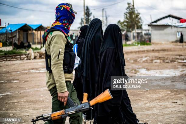 TOPSHOT Foreign women living in alHol camp which houses relatives of Islamic State group members walk under the supervision of a fighter of the...