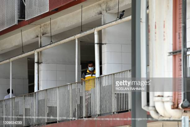 Foreign worker, wearing face mask as a preventive measure against the spread of the COVID-19 novel coronavirus, looks out from a window of the...