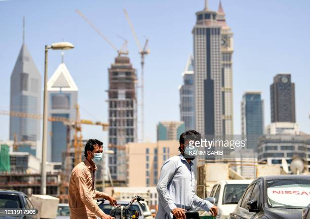 Foreign workers clad in mask due to the COVID-19 coronavirus pandemic walk pushing bicycles along a street in the Satwa district of Dubai on May 6,...