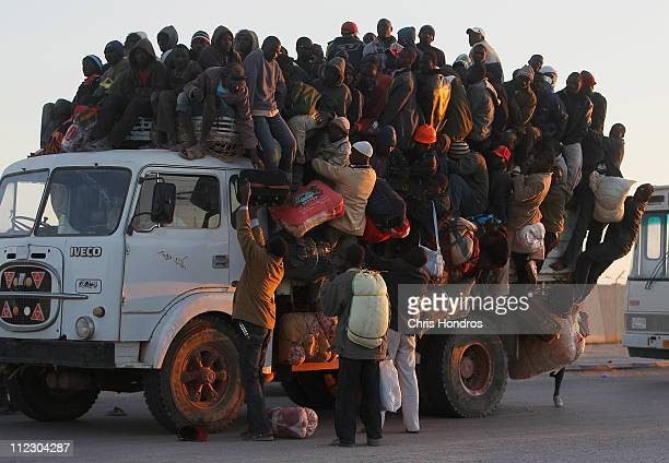 Foreign workers from Nigeria Ghana and other African countries pile in the back of a truck with their belongings trying to leave the besieged city of...