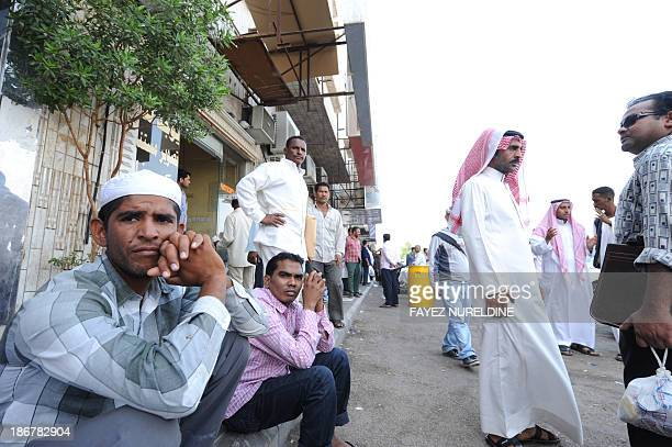 Foreign workers gather outside the Saudi immigration department waiting for an exit visa as Saudi security begin their search campaign against...
