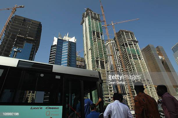 Foreign workers get on a bus near new highrise office buildings and hotels still under construction in the new City Center and West Bay district on...