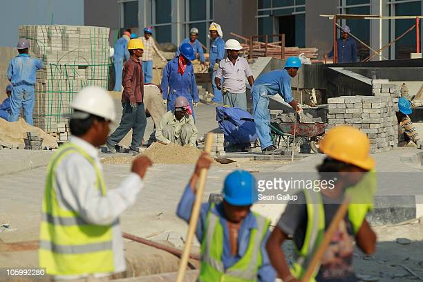 Foreign workers lay an entrance road at the construction site of a new hotel in the new City Center and West Bay district on October 24 2010 in Doha...