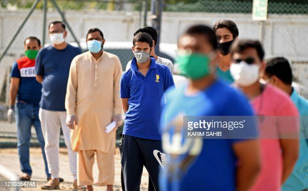 Foreign workers stand in line as they wait to be checked for the novel coronavirus at a testing centre in the Al Quaz area of Dubai in the United...