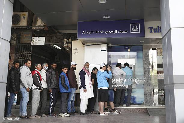 Foreign workers wait in line during a rest day to use the automated teller machine at the Al Rajhi Bank in Riyadh Saudi Arabia on Thursday Dec 1 2016...