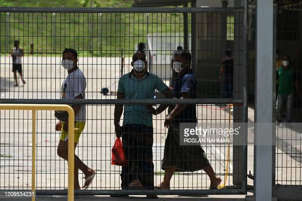 Foreign workers, wearing face masks as a preventive measure against the spread of the COVID-19 novel coronavirus, looks out from a fence of the...