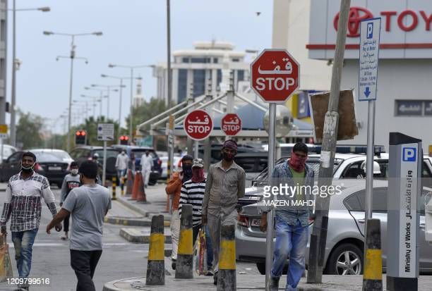 Foreign workers wearing protective masks amid the COVID-19 pandemic walk by in the old marketplace of the Bahraini capital Manama, on April 13, 2020.