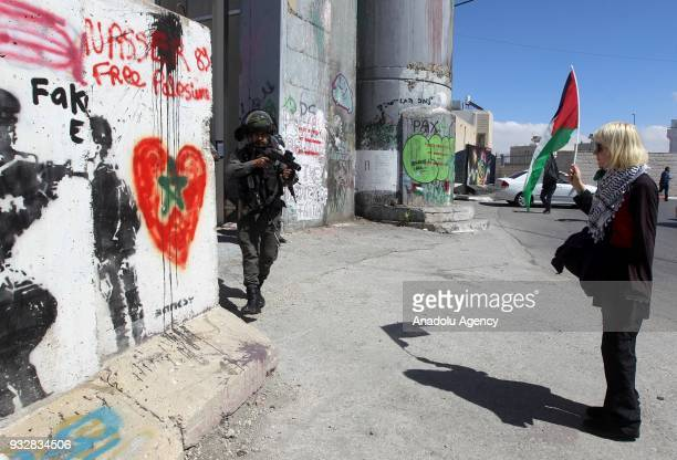A foreigner activist holds a Palestinian flag as she stands in front of an armed Israeli security force member during a protest against the US...