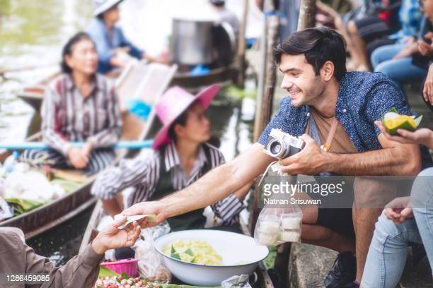 foreigner buying thai desserts from sailor who making food on a boat. - tourist stock pictures, royalty-free photos & images