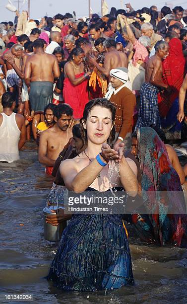 A foreigner devotee offering her prayer at the bank of Sangam confluence of river Ganga Yamnuna and mythical Saraswati on the occasion of Mauni...