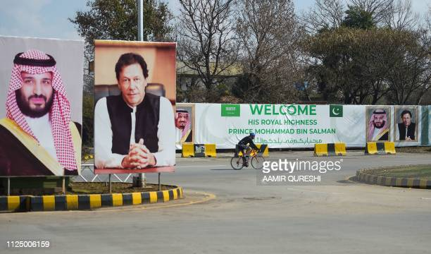 A foreigner rides past billboards showing portraits of Saudi Arabian Crown Prince Mohammed bin Salman and Pakistan's Prime Minister Imran Khan and a...