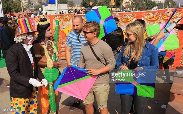 Foreigner tourists enjoy with dressed up artists during the Kite Festival on the occasion of Makar Sankranti at Jal Mahal in Jaipur Rajasthan India...