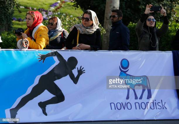 Foreigners and locals watch the first international Tehran marathon at Azadi Square in the Iranian capital on April 7 2017 Americans are among...