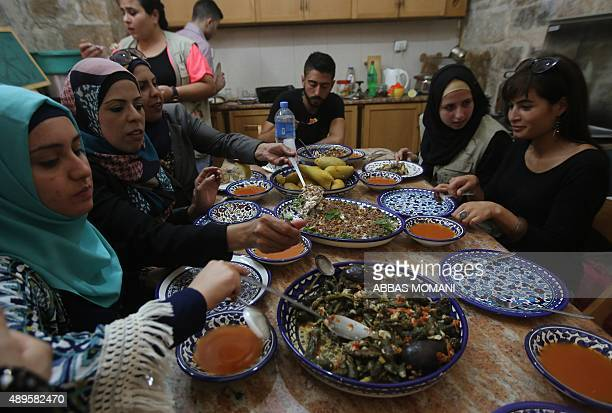 Foreigners sit down for a traditional Palestinian meal after preparing the food during a cooking class at the home of Fatima Kadumy in the West Bank...