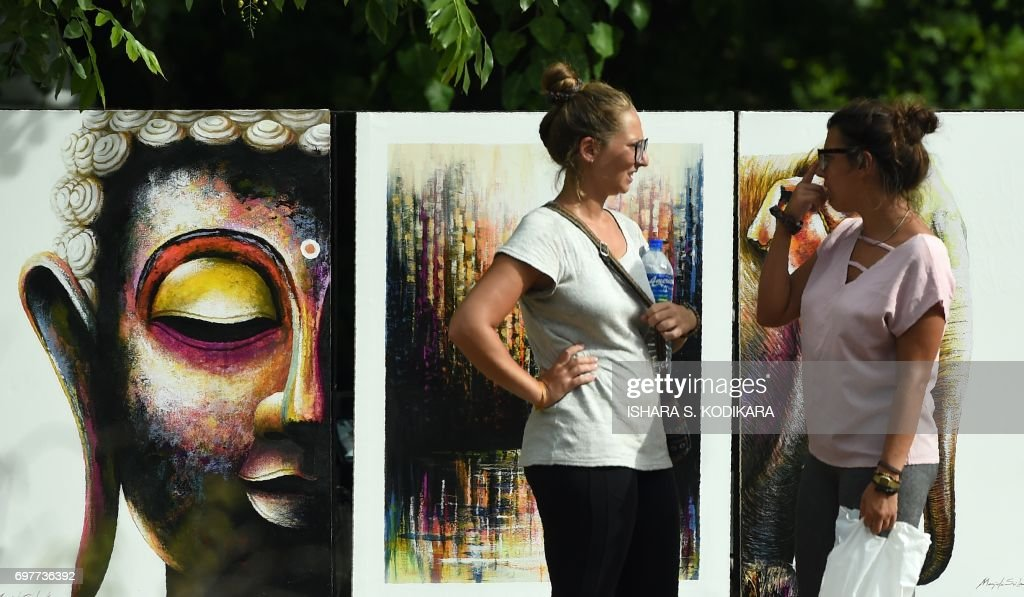 Foreigners walk past artwork near a roadside in the Sri Lankan capital Colombo on June 19,2017. Sri Lankan artists have turned the area near a park in the capital into an unofficial street for displaying local art. /