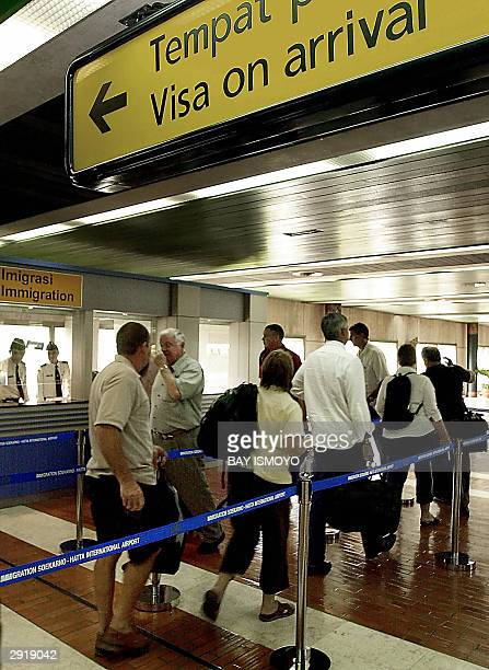 Foreigners walk through a special channel to the immigration counter to pay visa on arrival at Jakarta international airport in Banten 01 February...
