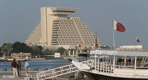 Foreigners walking along the Doha Corniche on September 22 2013 Three months after a new emir Sheikh Tamim bin Hamad AlThani stepped in Qatar's...