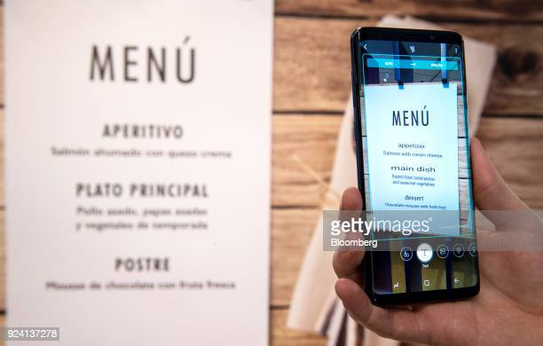 A foreignlanguage menu hangs on the wall as an attendee demonstrates the live language translation capability of the Galaxy S9 smartphone during a...