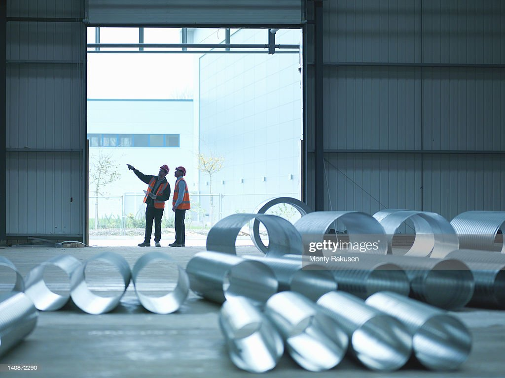 Foreman and apprentice in doorway in factory of building site : Stock Photo