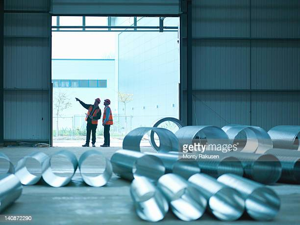 foreman and apprentice in doorway in factory of building site - metallic look stock pictures, royalty-free photos & images
