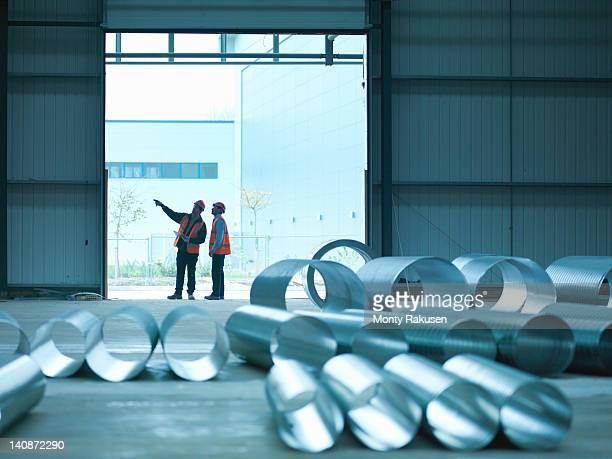 foreman and apprentice in doorway in factory of building site - stahl stock-fotos und bilder