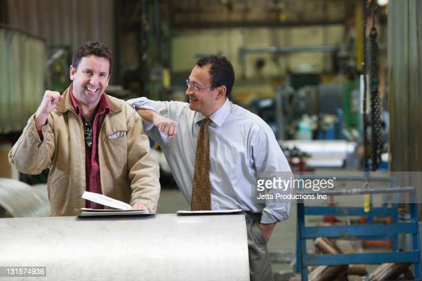 Foreman and worker cheering in factory