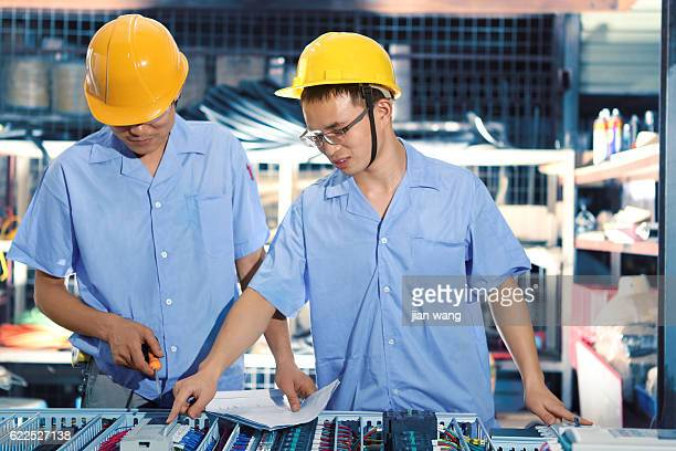 Foreman and worker reviewing blueprints in factory