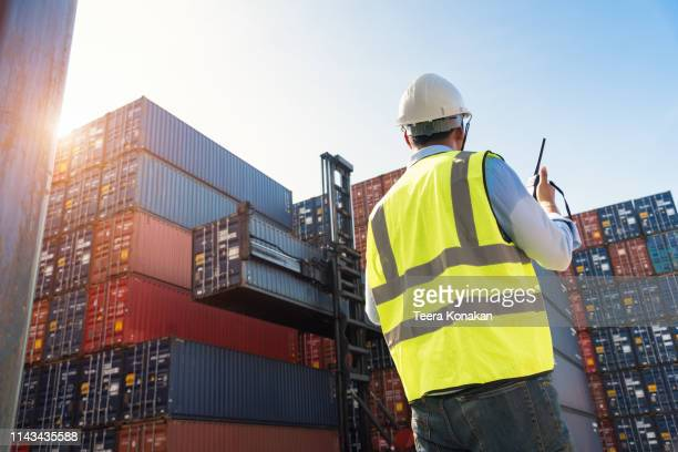 foreman control loading containers box from cargo freight ship - team captain stock pictures, royalty-free photos & images