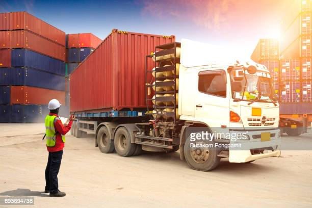 Foreman control loading truck in container depot, Containers box to truck for Logistic Import Export Background, Business logistic concept