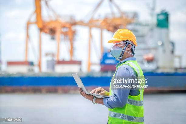 foreman controlling the loading of containers in the port to get into the cargo ship. - harbour stock pictures, royalty-free photos & images