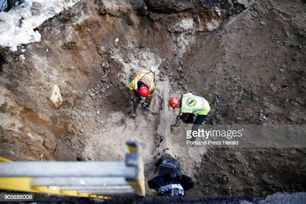 Foreman Greg Krummell left and Chris Stevens of Shaw Brothers Construction bury a new section of water main on Windham Center Road at the bridge over...