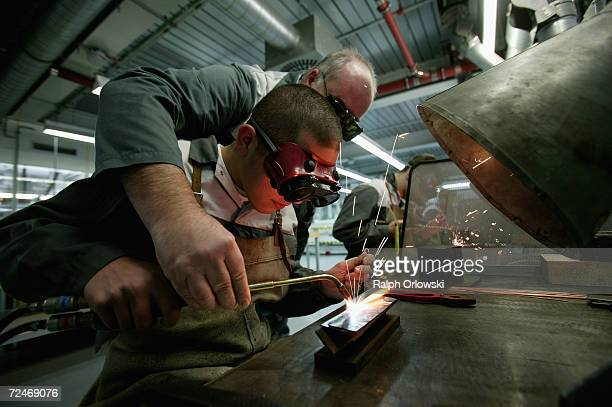 A foreman instructs a trainee in welding at the training center of German car maker Opel AG November 3 2006 in Ruesselsheim Germany In Germany...