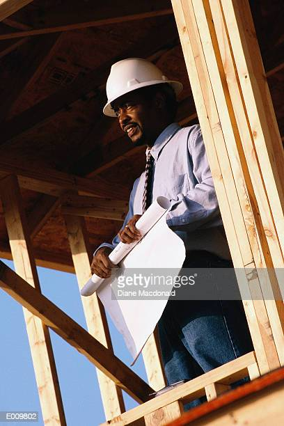 Foreman rolling up blue prints, looking out of building