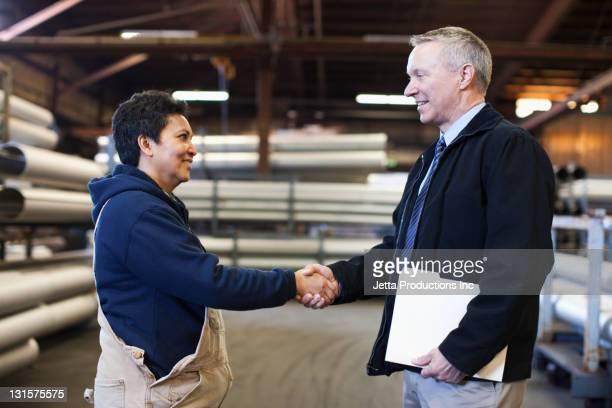 Foreman beim Händeschütteln mit Arbeiter in der Fabrik