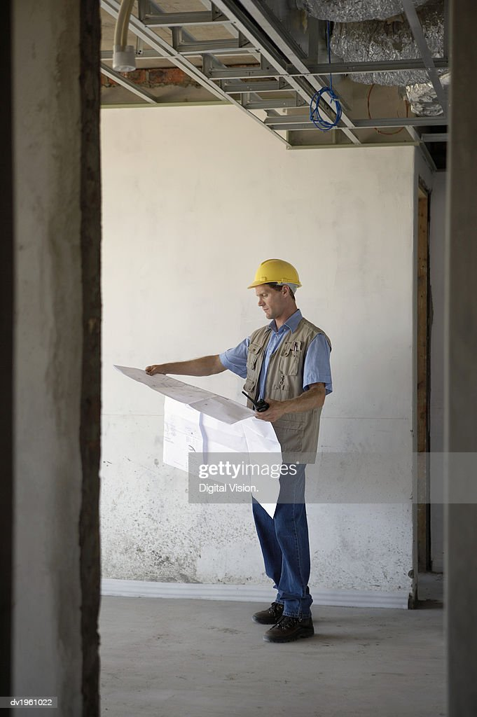 Foreman Stands in a Building Site Examining a Blueprint : Stock Photo