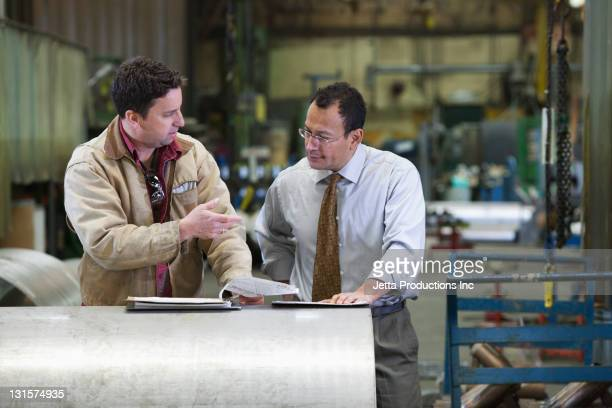 Foreman talking worker in factory
