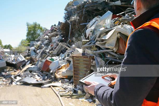Foreman using digital tablet at scrap metal recycling plant