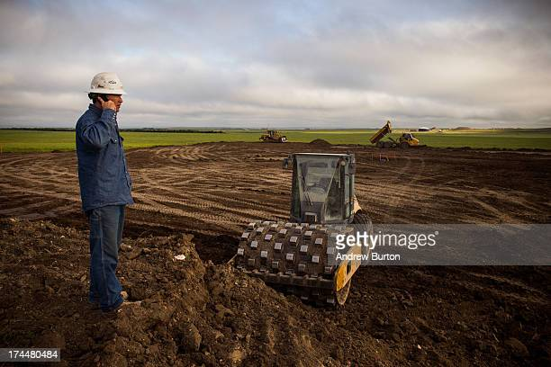 A foreman with JMac Resources reviews a site being cleared for construction in the middle of a canola field on July 26 2013 outside Williston North...