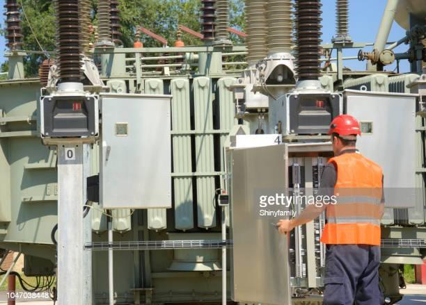 Foreman working in power station, near transformer.