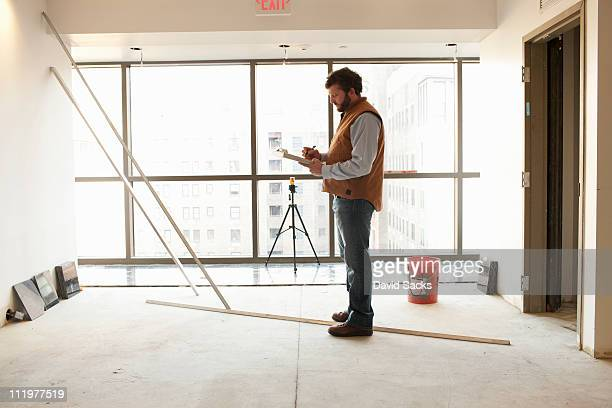 foreman writing on clipboard at construction site - building contractor stock pictures, royalty-free photos & images