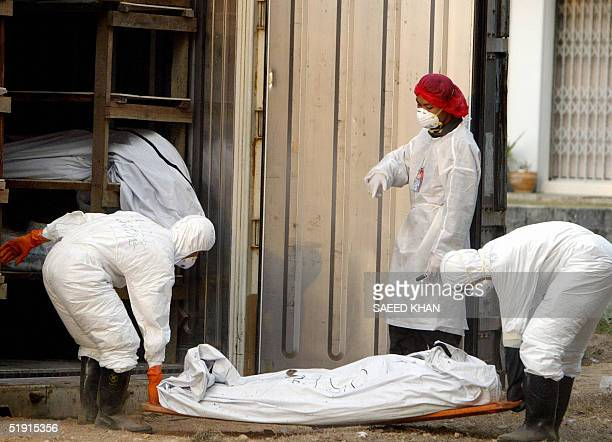 Forencis workers place back a dead body after some other tests in a refrigerated container at Ban Muang temple in Takua Pa 05 January 2005 Forensic...