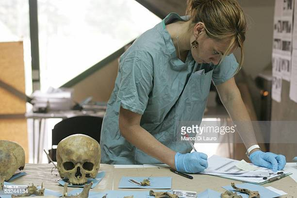 Forensic anthropologist KerryAnn Martin of Great Britain examines a cranium exhumed from a mass grave at the International Commission on Missing...